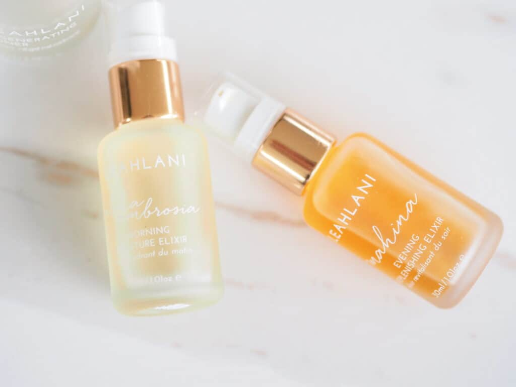 Bottle of Leahlani Skincare Aloha Ambrosia elixir review and Mahina elixir on counter for product review