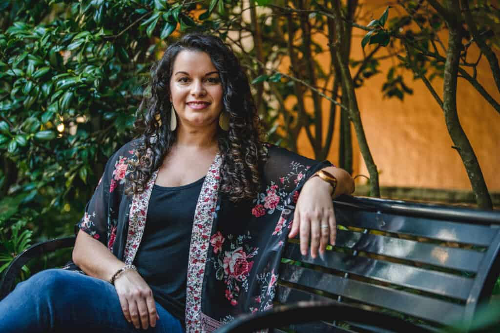 Clean beauty blogger curly hair expert Delilah Orpi sitting on bench in a garden facing the camera smiling