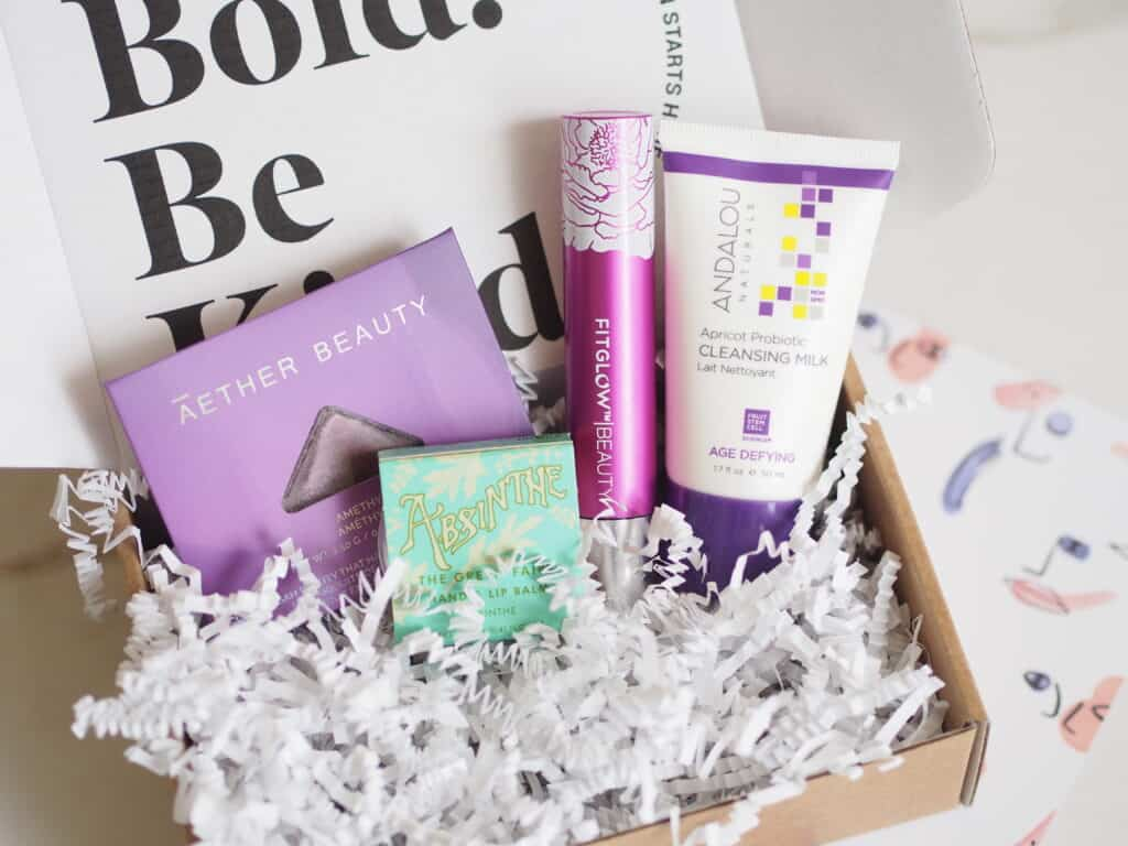 Clean green beauty samples shown in box with packing ribbon on table