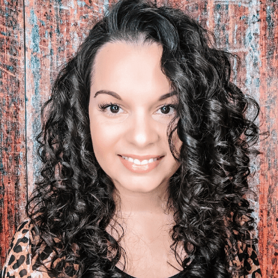 Delilah Orpi 2b 2c 3a curls expert and clean beauty consultant smiling with big curls and a reddish background