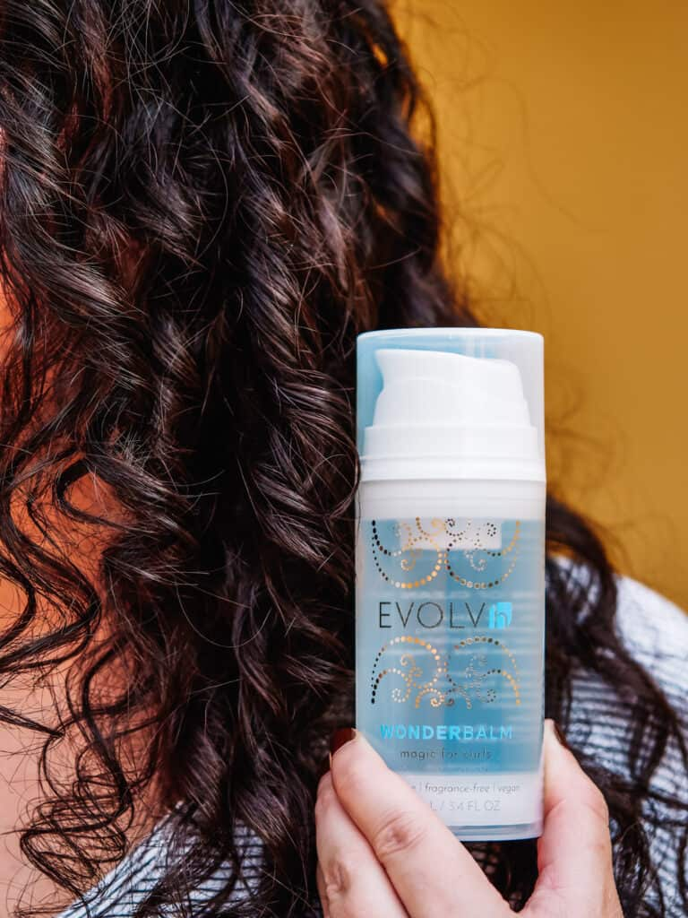EVOLVh WonderBalm Magic For Curls bottle next to curly hair
